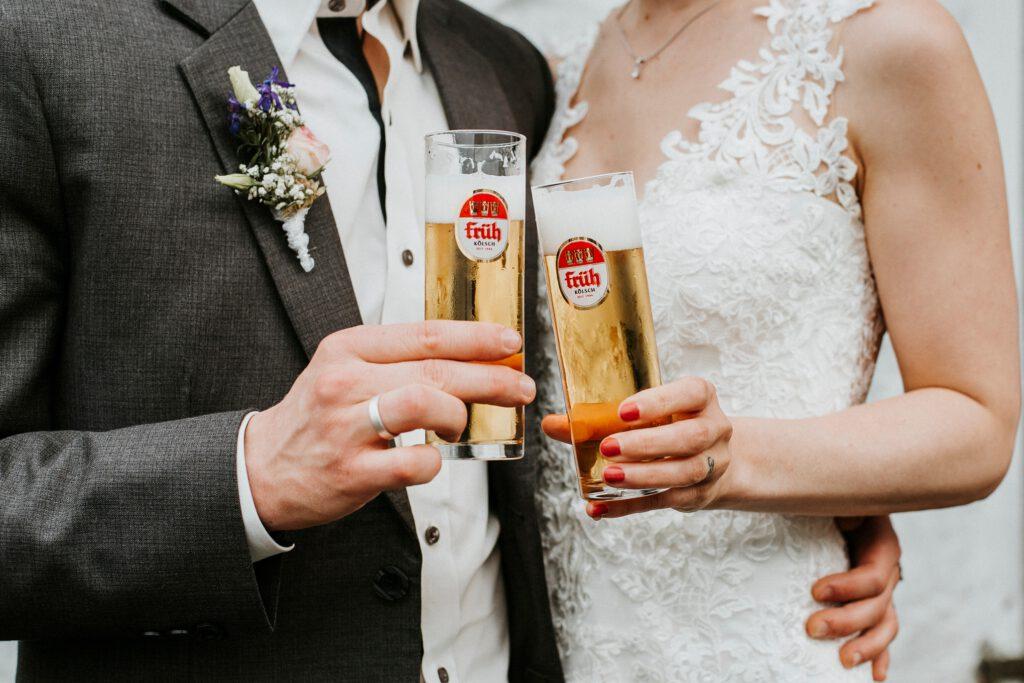 Ein Brautpaar hält zwei früh Kölsch Biergläser